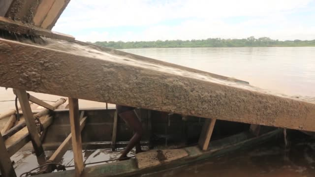 LS Men mine for gold on a river barge The region of Madre de Dios in SouthEastern Peru has been devastated by illegal gold mining it has a...