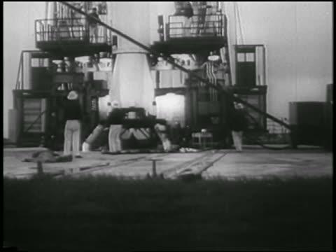vídeos de stock e filmes b-roll de b/w 1958 men near bottom of rocket carrying first us satellite explorer i on launch pad - 1958