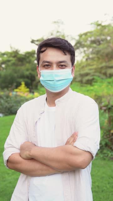 vidéos et rushes de les hommes d'origine asiatique, âgés de 30 à 40 ans, portent des vêtements décontractés et portent des masques pour prévenir la maladie du coronavirus. - vidéo portrait