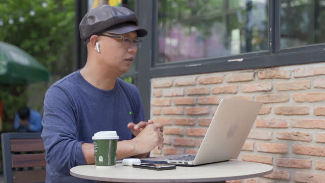 men of asian descent, aged 40-50, work and drink coffee in a coffee shop. - coffee drink stock videos & royalty-free footage