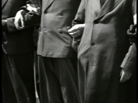 vidéos et rushes de men of the croixdefeu organization standing w/ arms linked showing arm band w/ skull blade men of the croixdefeu marching in street men's legs in... - 1934