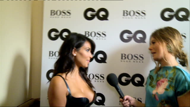 Arrivals and interviews Kim Kardashian West posing backstage with GQ Award for Woman of the Year and Jonah Hill coming through door in background /...