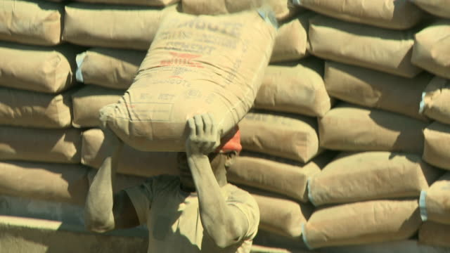 ms men offloading bags of cement from a truck nigeria is home to nearly 200 million people which has earned it the name giant of africa it is an oil... - unloading stock videos & royalty-free footage