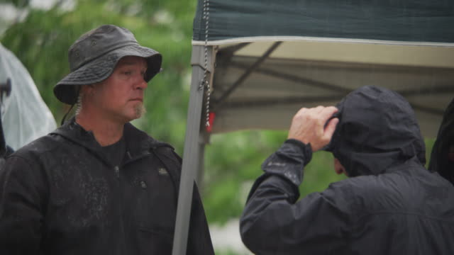 men on a motion picture crew wearing raincoats stand under a pop-up tent in a rainstorm. - waterproof clothing stock videos & royalty-free footage