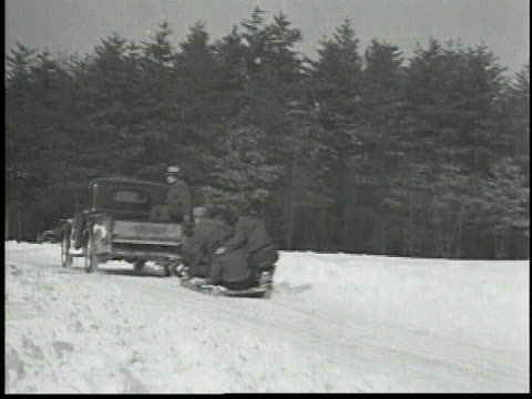 men on a sled being pulled by a truck / truck pulls sled across snow / teams of men in a tug of war contest / one team is pulled across a snow bank /... - 1934 stock-videos und b-roll-filmmaterial