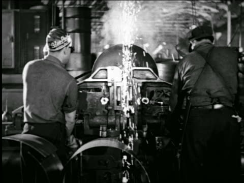 b/w 1943 rear view men on assembly line making steel oil drums / industrial - stahlfass stock-videos und b-roll-filmmaterial