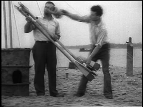b/w 1933 2 men on beach preparing for launch of world's first liquidfueled rocket / newsreel - 1933 stock videos and b-roll footage
