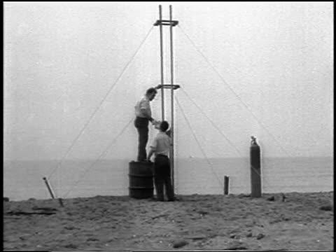 vídeos y material grabado en eventos de stock de men on beach preparing for launch of world's first liquid-fueled rocket / newsreel - 1933