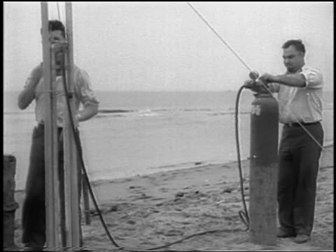 B/W 1933 2 men on beach preparing for launch of world's first liquidfueled rocket / newsreel