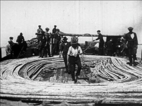 b/w 1923 men on boat laying phone cable in ocean (longest, between havana + key west) / documentary - wire stock videos & royalty-free footage