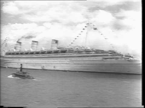men on deck of queen mary / queen mary passing statue of liberty / sign on shore reading welcome home well done / queen mary / queen mary passing new... - new york harbor stock videos & royalty-free footage