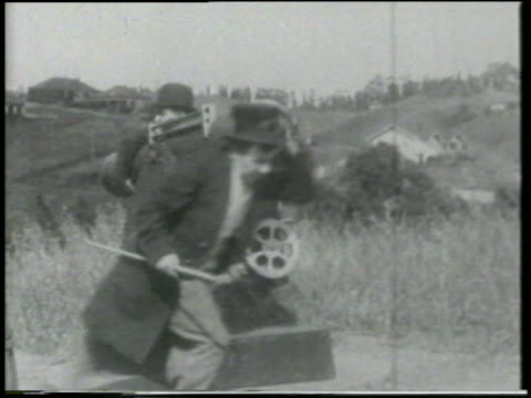 stockvideo's en b-roll-footage met b/w 1915 2 men (1 is chester conklin) on grassy hill preparing to fire cannon / feature - 1915