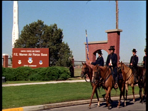 men on horseback in traditional us soldier uniforms zoom out to soldiers riding past the cheyenne fe warren us air force base with planted missile statues - cavalleria video stock e b–roll