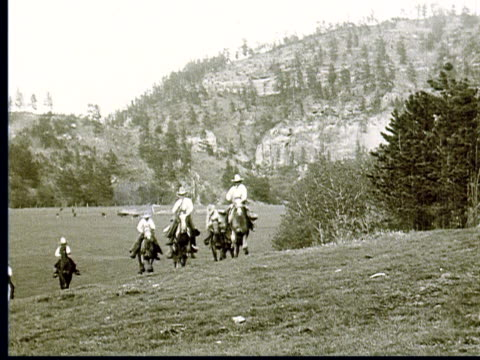 1924 B/W MONTAGE Men on horses wearing cowboy hats gallop over hill towards camera, herd of horses running / South Dakota, USA