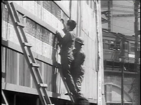 Men on ladders posting returns
