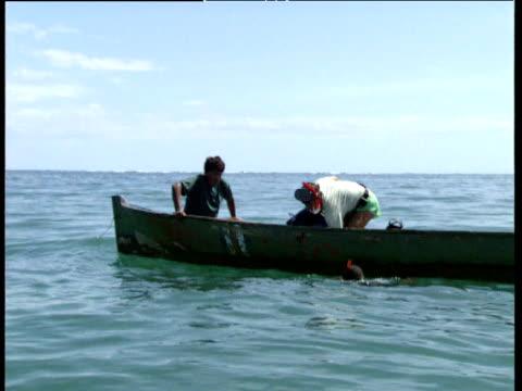 men on small fishing boat at sea prepare snorkelling equipment trinidad and tobago - trinidad trinidad and tobago stock videos & royalty-free footage