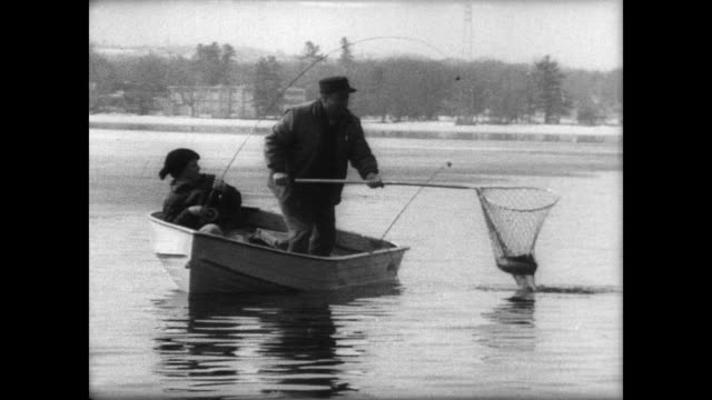 Men on small fishing boats casting lines at the beginning of the fishing season in the Northeast / man nets a fish and scoops it into the boat / boy...