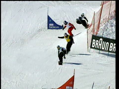men on snowboards jump over ramps and down ski slope in snowboard competition then congratulate each other at finish switzerland - huvudbonad bildbanksvideor och videomaterial från bakom kulisserna