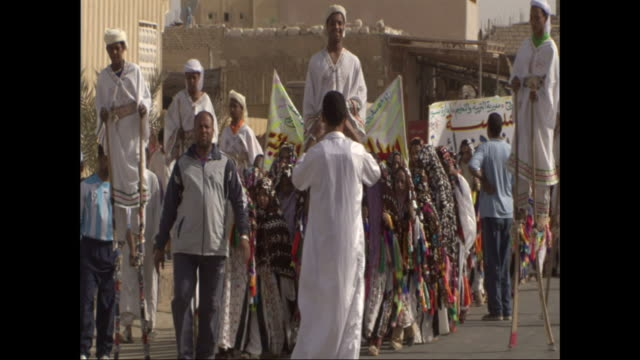 men on stilts walk in front of children in decorated robes during a street parade in egypt. - stilts stock videos and b-roll footage