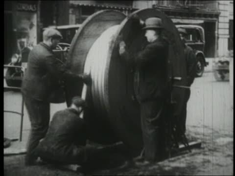 B/W 1930 men on street unwinding huge spools of telephone wires