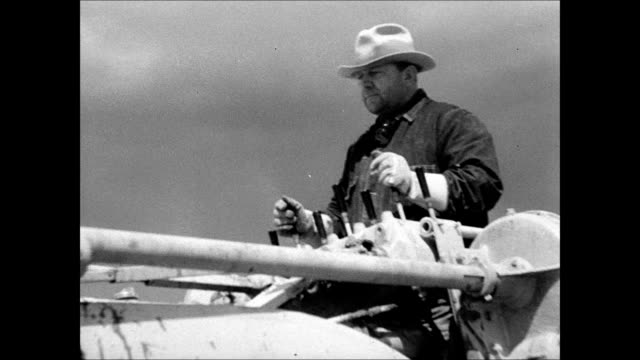 men on tractors terracing contouring land pulling machines leveling scrub land vs men using machine to strip cut sod stacking placing cubes onto... - dust bowl stock videos and b-roll footage