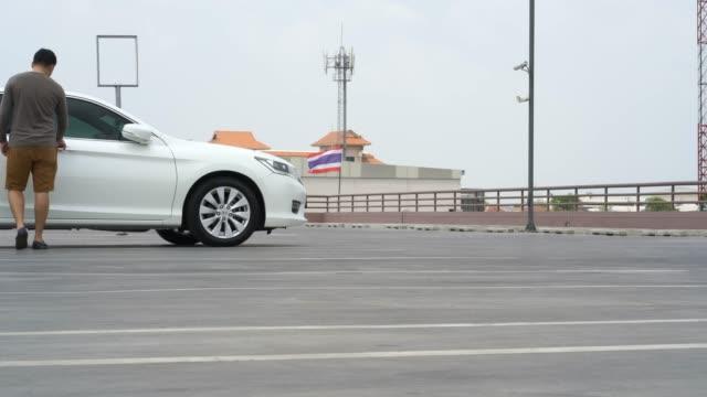 男性は駐車場で車のドアを開けます。 - 駐車点の映像素材/bロール
