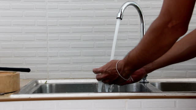 Men open wafer at valve of sink