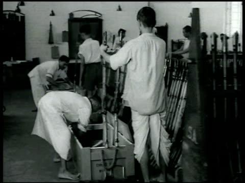 vidéos et rushes de men operating levers room filled w/ completed rifles men boxing up rifles male worker inspecting artillery shell casing - levier de contrôle