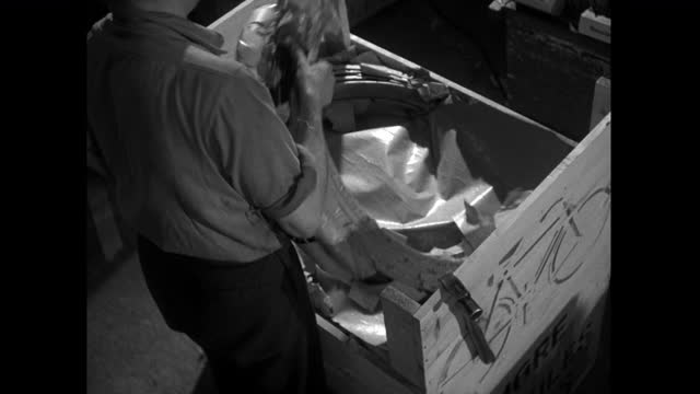 men pack bicycle parts into wooden crate for export; 1952 - production line worker stock videos & royalty-free footage