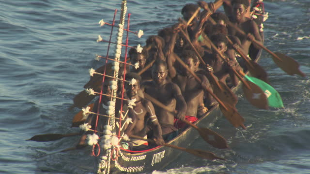 Men paddle war canoes, Solomon Islands