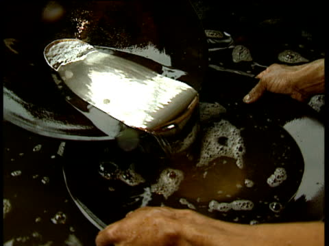 men pan gold particles mixed with mercury from one pan to another gradually separating alta floresta brazil; 1993 - liquid stock videos & royalty-free footage