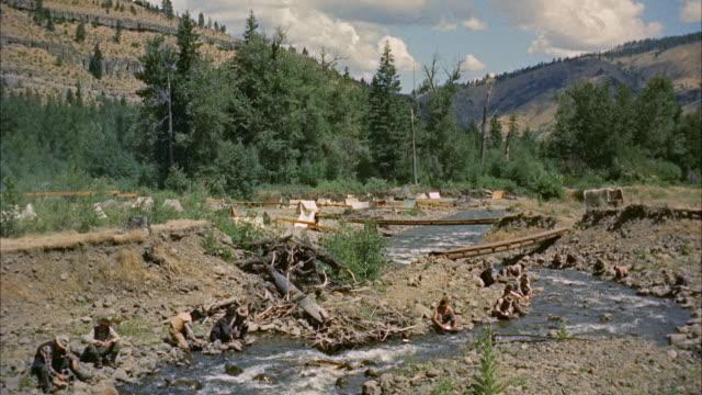 vidéos et rushes de ws men panning for gold along narrow stream leading toward town - panning
