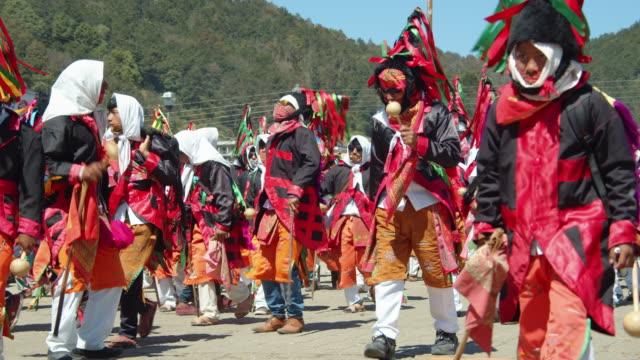 men parading in colorful traditional attires during a festival in san juan chamula, chiapas, mexico - antico condizione video stock e b–roll