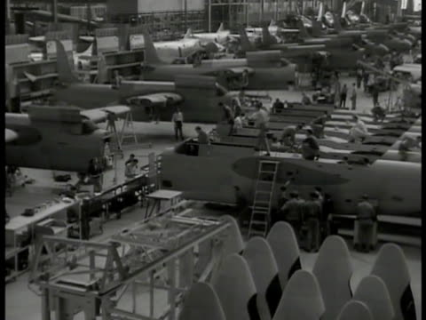 men passing gate guard checking id. men working on incomplete airplanes. two mechanics working on engine. men moving howitzer piece w/ crane. workers... - howitzer stock videos & royalty-free footage