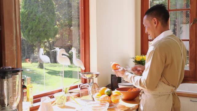 vídeos de stock e filmes b-roll de ms men peeling carrot in kitchen / fujikawaguchiko, yamanashi, japan - vida simples