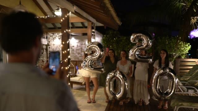 vídeos de stock, filmes e b-roll de homens que fotografam meninas com balão 2020 no ano novo na casa de praia - pátio