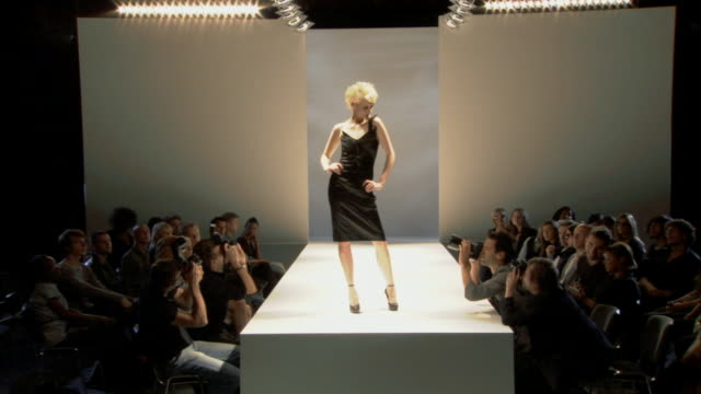 WS Men photographing model in black dress on catwalk while audience watches / London, England, UK
