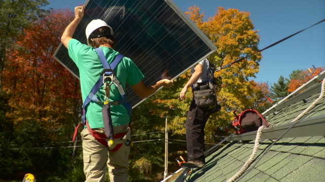 ws men picking up solar panel and taking it to the end of the roof and setting it down / greenfield, massachusetts, usa - positioning stock videos & royalty-free footage