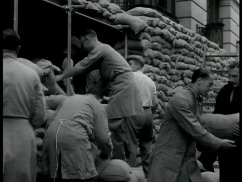 men piling sandbags wall of stacked sandbags bg. soldiers walking on street children & advertisement posters bg. men digging trench using pick axe... - 1939 stock-videos und b-roll-filmmaterial