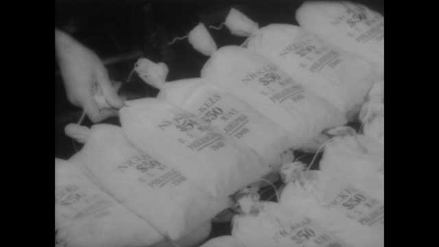 1940 men place coins into $50 sacks - money press stock videos and b-roll footage