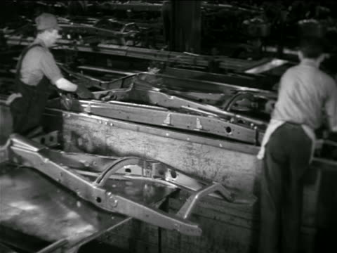 b/w 1936 2 men placing metal frame on conveyor belt in chevrolet car factory - chevrolet stock videos & royalty-free footage