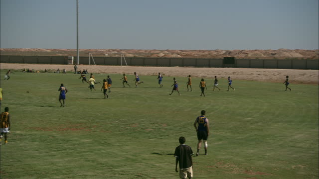 men play a game of footy on a grassy field. - team sport stock videos & royalty-free footage