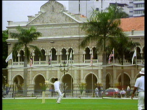 stockvideo's en b-roll-footage met men play cricket wearing full whites and padding on plush green lawn - 1992