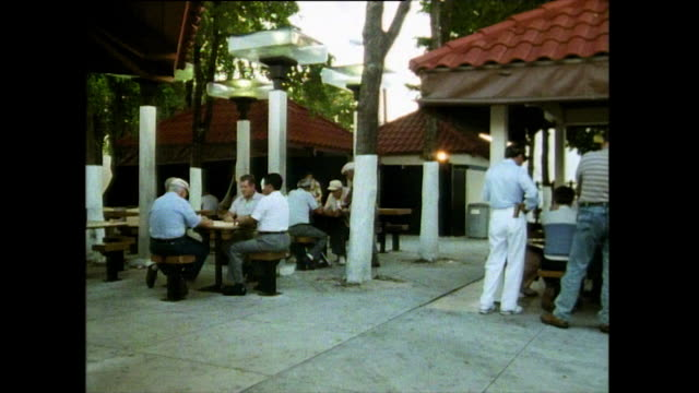 vídeos de stock, filmes e b-roll de men play dominoes outdoors in little havana; 1991 - williamsburg new york