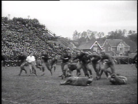 1925 WS Men play football game and run down the field while crowds watch / United States