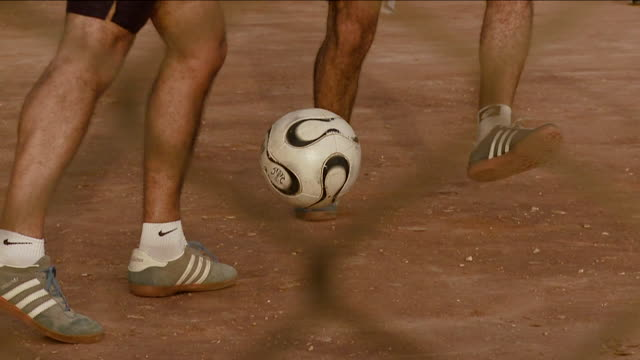 Men play soccer at a playground in Egypt. Available in HD.