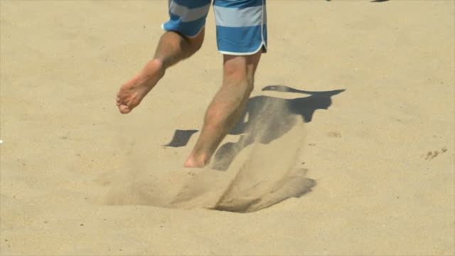 stockvideo's en b-roll-footage met men playing a beach volleyball game match in the sand. - slow motion - men