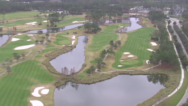 vídeos y material grabado en eventos de stock de aerial ws zi men playing at golf course / florida, united states - bandera de golf