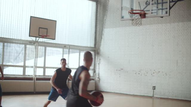 Mannen spelen basketbal binnen 2 op 2