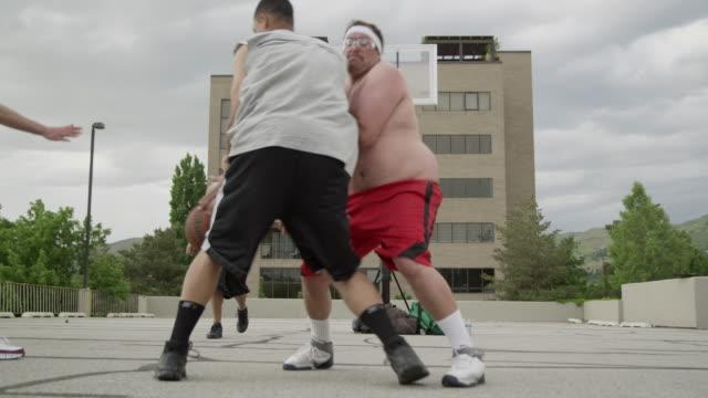 WS Men playing basketball, man falling in foreground / Salt Lake City, Utah, USA.
